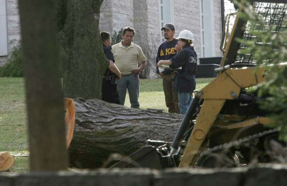 A federal Occupational Health and Safety Administration official, in white helmet, speaks with a Greenwich police officer and tree service workers on the property of 537 North St. on Friday after one of the workers was seriously injured. Photo: David Ames, David Ames/For Greenwich Time / Greenwich Time Freelance