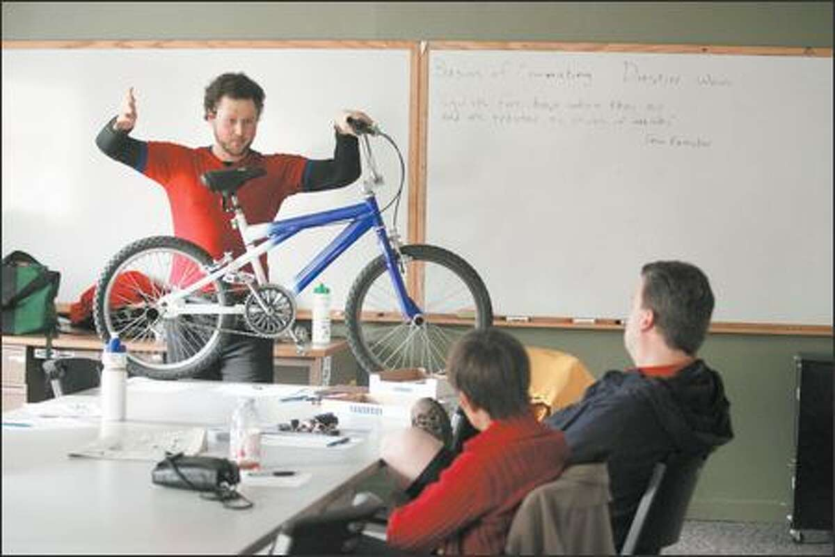Students Lisa Haff and Chris Collison listen to Cascade Bicycle Club instructor Dustin Wood talk about equipment during a class on bicycle commuting, with the aim of making biking to work as practical as possible.