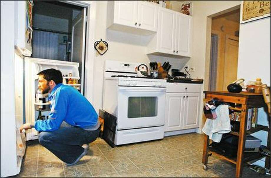 Peter Nevin, a crew supervisor with the Washington Conservation Corps, looks for a snack in the home he was able to buy with help from a city housing program. Photo: Gilbert W. Arias/Seattle Post-Intelligencer