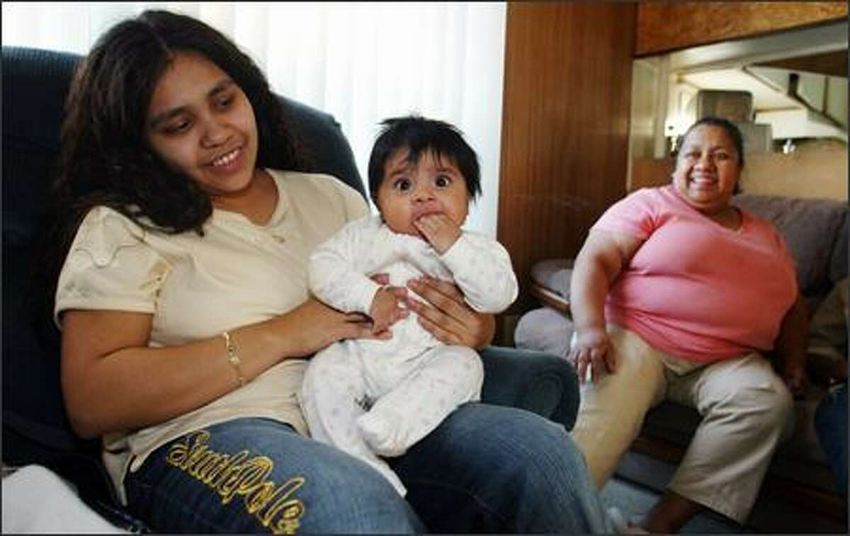 Estella Pineda, left, shows off her daughter, Kimberly, 3 1/2 months, as mother Narciza Pineda looks on. Narciza Pineda, a Space Needle janitor, saw her wages rise slightly since the Seattle P-I series started.