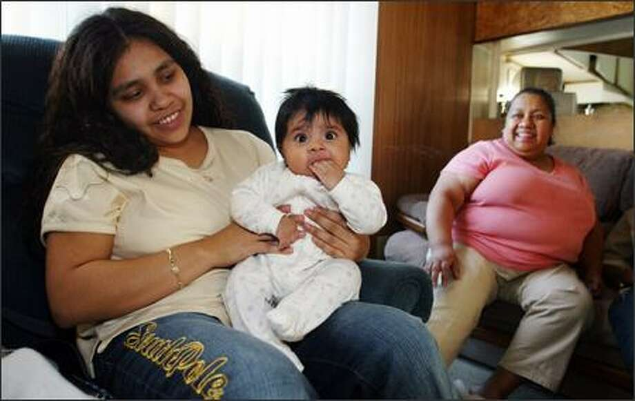 Estella Pineda, left, shows off her daughter, Kimberly, 3 1/2 months, as mother Narciza Pineda looks on. Narciza Pineda, a Space Needle janitor, saw her wages rise slightly since the Seattle P-I series started. Photo: Gilbert W. Arias/Seattle Post-Intelligencer