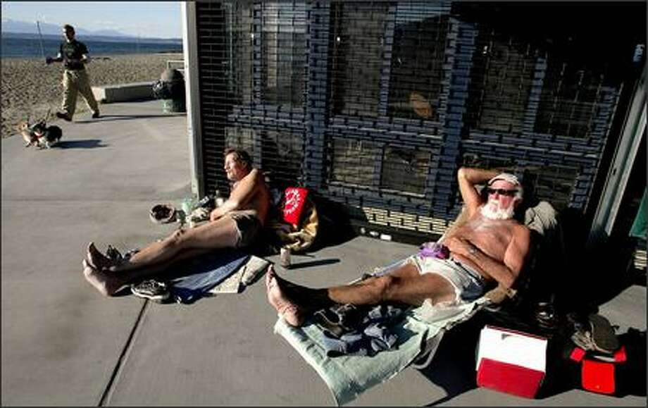 Art Foss, right, and Al Ochs use a building for a windbreak as they sunbathe at Golden Gardens Park. Temperatures hovered Wednesday around 45 degrees, but chillier weather is expected for the rest of the week. Photo: Gilbert W. Arias/Seattle Post-Intelligencer