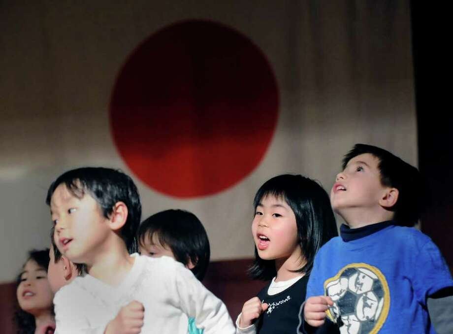 "Greenwich Japanese School student Suzuha Maki, 5, second from right, performs the song, ""Tomorrow,"" with her classmates during the Japan Earthquake and Tsunami Charity Concert at the Greenwich Japanese School, Friday night, March 18, 2011. Photo: Bob Luckey / Greenwich Time"