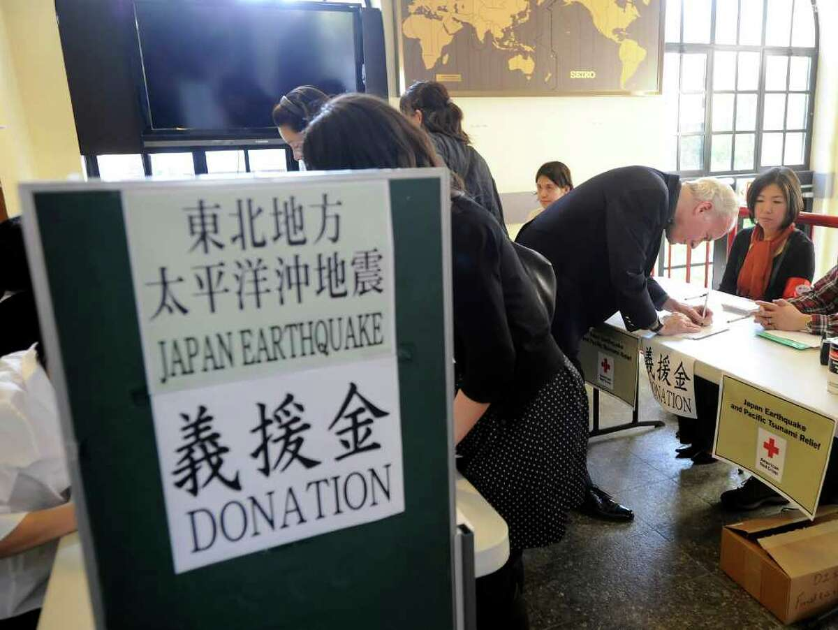 William Jarvis of Greenwich donates money during the Japan Earthquake and Tsunami Charity Concert at the Greenwich Japanese School Friday night, March 18, 2011.