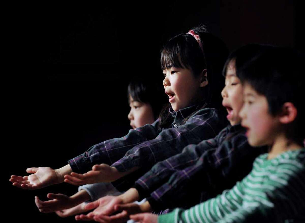 Greenwich Japanese School kindergartener Hinako Isogami, 6, performs a song with her classmates during the Japan Earthquake and Tsunami Charity Concert at the Greenwich Japanese School, Friday night, March 18, 2011.
