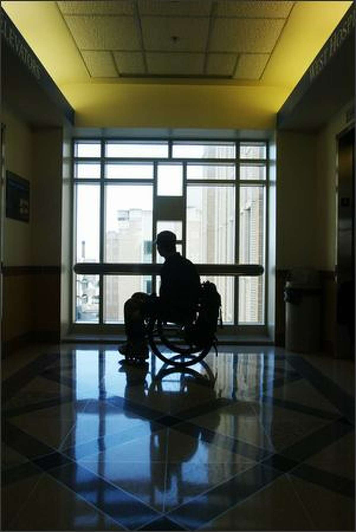Brian Chaffin, 25, who broke his back three years ago and spent months at Harborview, pauses in a hallway. During his recovery, natural light and skyscapes were solace for Chaffin; his photo is at top.