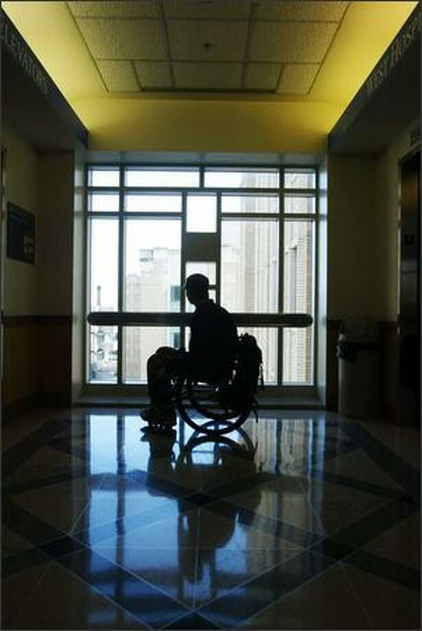 Brian Chaffin, 25, who broke his back three years ago and spent months at Harborview, pauses in a hallway. During his recovery, natural light and skyscapes were solace for Chaffin; his photo is at top. Photo: Gilbert W. Arias/Seattle Post-Intelligencer