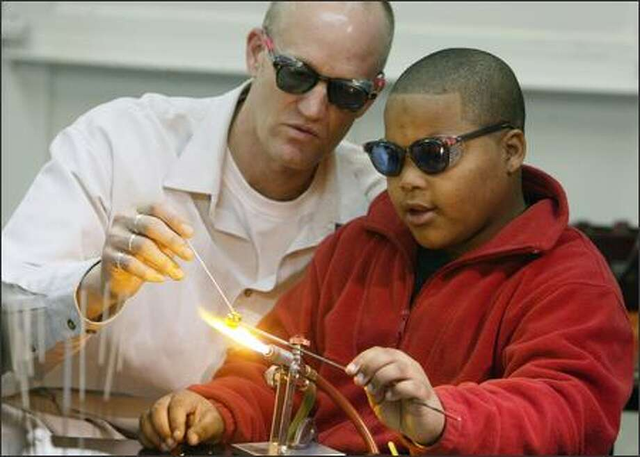 Twelve-year-old Raul puts the flame to his glass bead project at the Pratt Fine Arts Center with a little help from his Washington Middle School teacher Brad Erben. Photo: MIKE URBAN/P-I