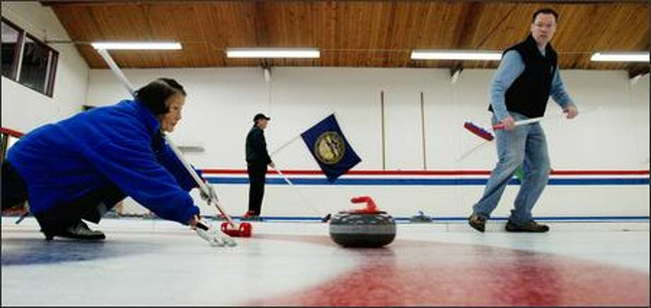 "At Seattle's Granite Curling Club, Betty Kozai delivers a rock as teammate Dan Boerner prepares to ""sweep,"" or brush, the ice to help the rock travel farther. Photo: DAN DELONG/P-I"