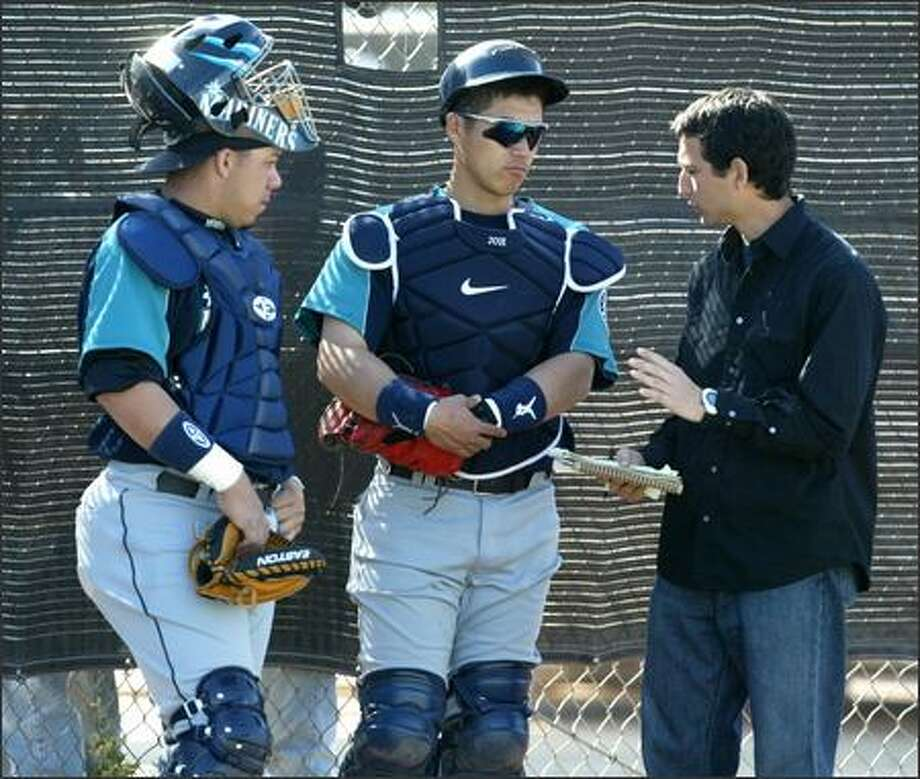 Rookie Rene Rivera, left, and Japanese veteran import Kenji Johjima compare notes with help from translator Ken Barron. The two catchers converse in a mix of Japanese, English and Spanish. Photo: Scott Eklund/Seattle Post-Intelligencer