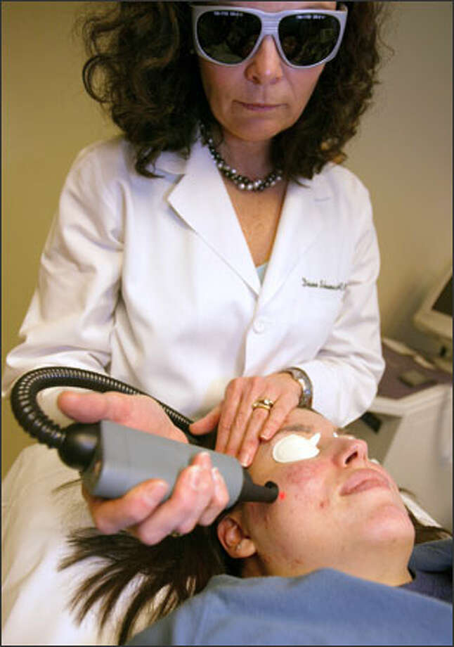 Diane Schumacher uses an Aramis laser to treat acne for Teressa Aliberti, 24, at Seattle's Madison Skin and Laser Center. The past 10 years have seen an increase in ways doctors can treat acne. Photo: Grant M. Haller/Seattle Post-Intelligencer / Grant M. Haller