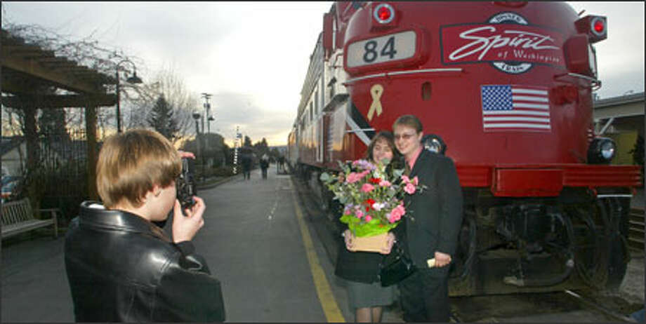 Slava and Vladimir Karabut of Everett pose for son Alex with the Spirit of Washington dinner train, which may close. Photo: Karen Ducey/Seattle Post-Intelligencer