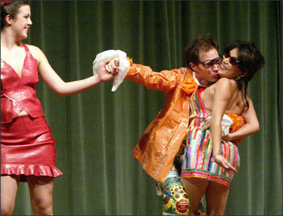 With eyeglasses askew from a forceful kiss, Seattle City Councilman Peter Steinbrueck plays up his Austin Powers persona with models dressed in the remains of a yoga exercise ball and concert wristbands at the Seattle Asian Art Museum's Trash Fashion Bash. Photo: Mike Urban/Seattle Post-Intelligencer / Seattle Post-Intelligencer