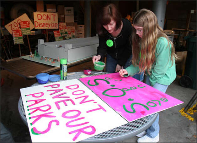 Diane Duthweiler paints a sign in her garage with neighbor Clara Manahan, 10, for a rally Saturday against Seattle Parks and Recreation. Organizers say the department runs roughshod over residents in making decisions. Photo: Meryl Schenker/Seattle Post-Intelligencer / SEATTLE POST-INTELLIGENCER