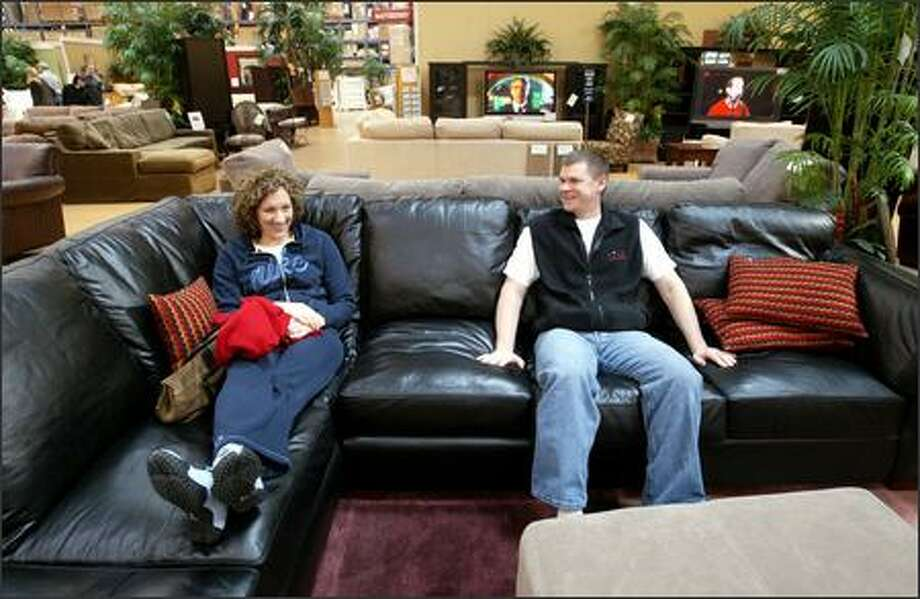 Shoppers Janice and Bryan Evans of Fall City test out a leather sectional Friday in the Costco Home store in Kirkland. Costco may one day add dedicated furniture sections to its traditional stores. Photo: DAN DELONG/P-I
