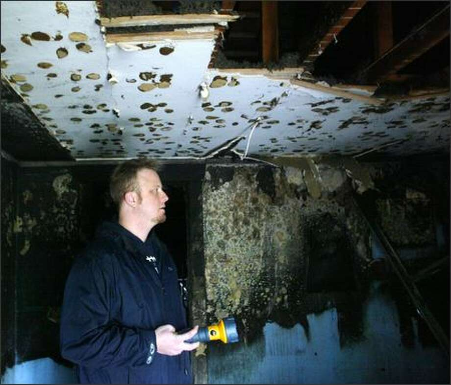 Todd Downing checks on the remains of his home which caught fire on February 14, 2006. He and his two children have endured many hardships over the past year including the death of his wife, the death of Todd's father, and a flood of sewage to their home on Christmas Eve. Now the family is living in a rental home across the street. (PI photo/Karen Ducey) Photo: Karen Ducey/Seattle Post-Intelligencer