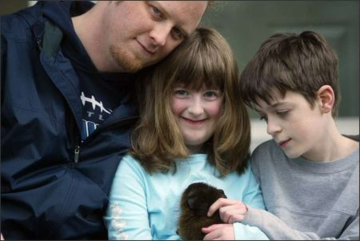 Todd Downing and his two children, Kayleigh,8, and Tyler,11, of West Seattle have endured many hardships over the past year including the death of Sam, his wife and their mother,the death of Todd's father, a flood of sewage to their home on Christmas Eve and a fire which destroyed the home on Valentines Day 2006. Now the family is living in a rental home across the street. (PI photo/Karen Ducey)
