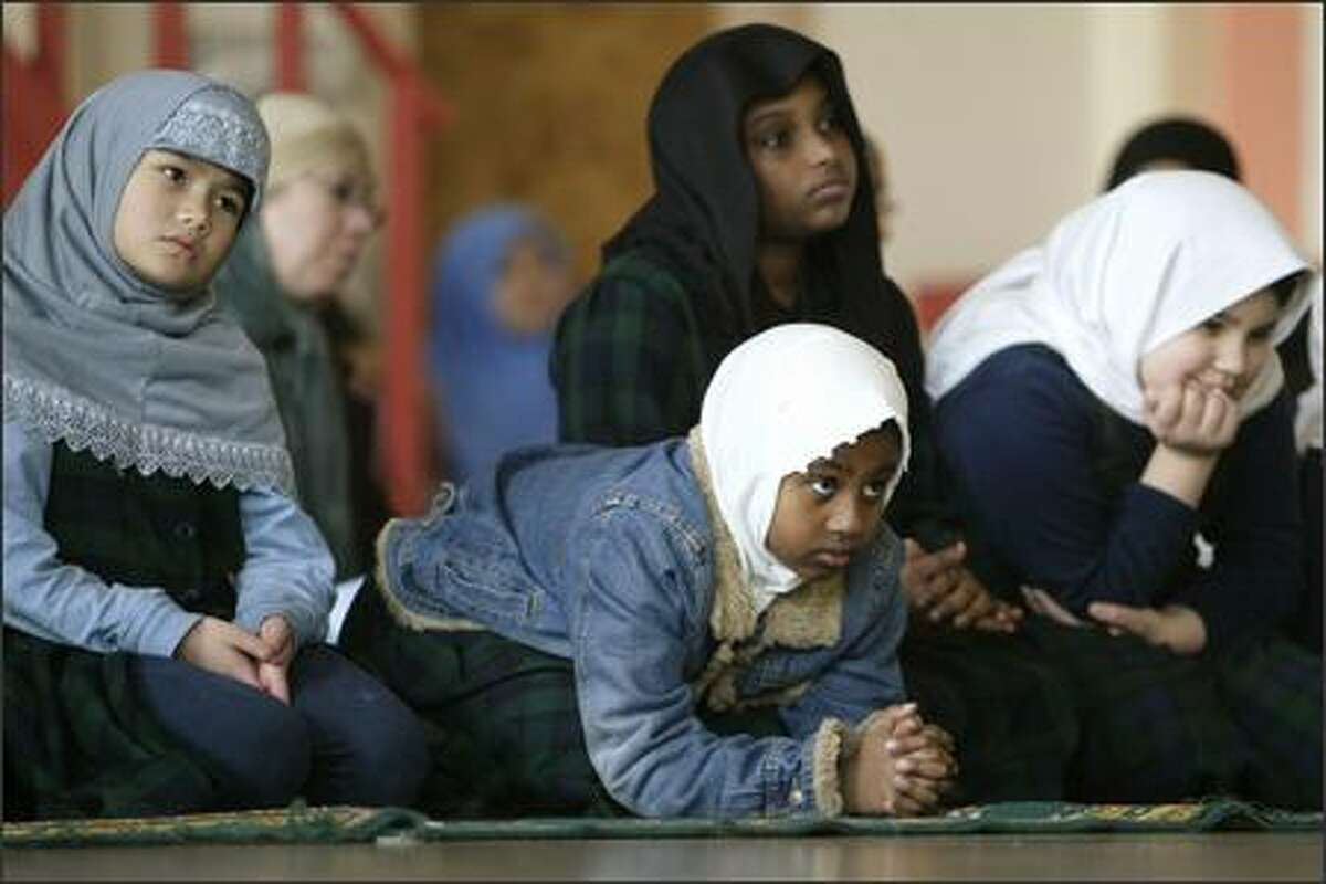 Yasmine Ahmach, 8, and other students at the Islamic School of Seattle listen during prayers at the school on Friday.