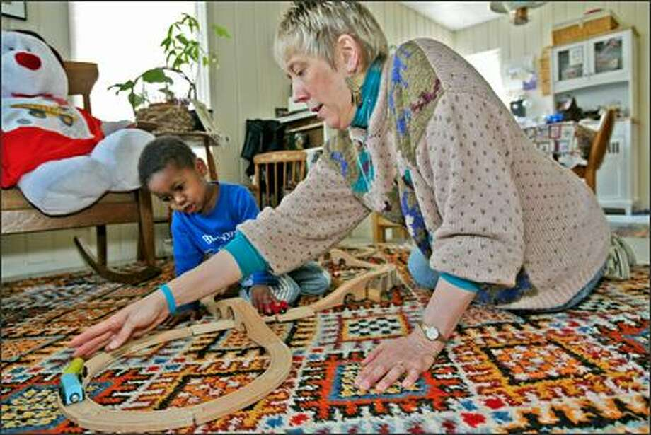Jane Fairchild and her son, Luke, play with a train set in the Rainier Valley home Fairchild bought with the help of a Homestead Community Land Trust. Photo: GRANT M. HALLER/P-I