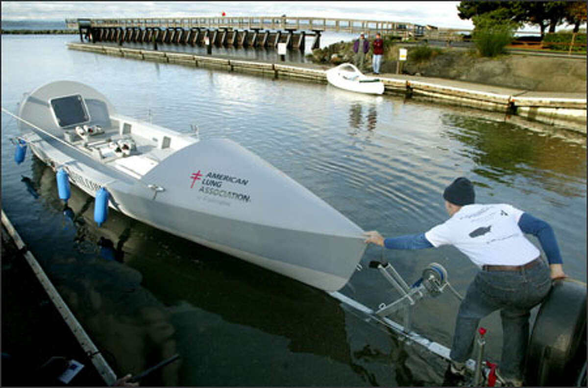 Dylan LeValley helps launch the 29-foot boat he and three friends plan to row across the Atlantic Ocean as the first American team to compete in the Atlantic Ocean Fours Race.