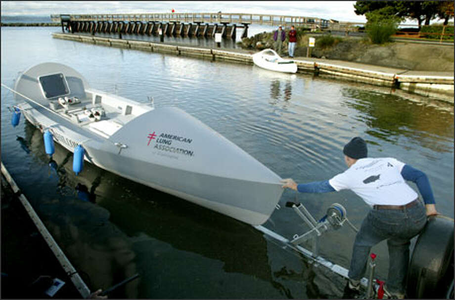 Dylan LeValley helps launch the 29-foot boat he and three friends plan to row across the Atlantic Ocean as the first American team to compete in the Atlantic Ocean Fours Race. Photo: Gilbert W. Arias/Seattle Post-Intelligencer / Seattle P-I