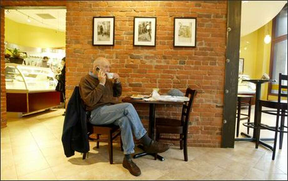 Alan Zelina, in town on business from Ohio, enjoys a latte at Caffe Umbria. If you prefer to take your espresso standing up, feel free to lean against the bar as the Italians do. Photo: Scott Eklund/Seattle Post-Intelligencer