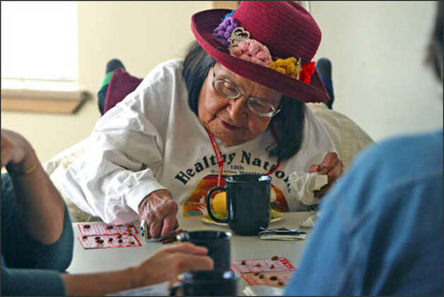 Alma Chastain picks up a bean to place on a bingo card at the Seattle Indian Health Board at 611 12th Ave. S. Photo: Grant M. Haller/Seattle Post-Intelligencer / Grant M. Haller