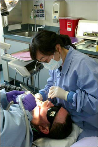 Dr. Mi Young Chang works on John Eagan's teeth, part of the services offered by the Seattle Indian Health Board. Assisting at left is Somrak Jaion. Photo: Grant M. Haller/Seattle Post-Intelligencer / Grant M. Haller