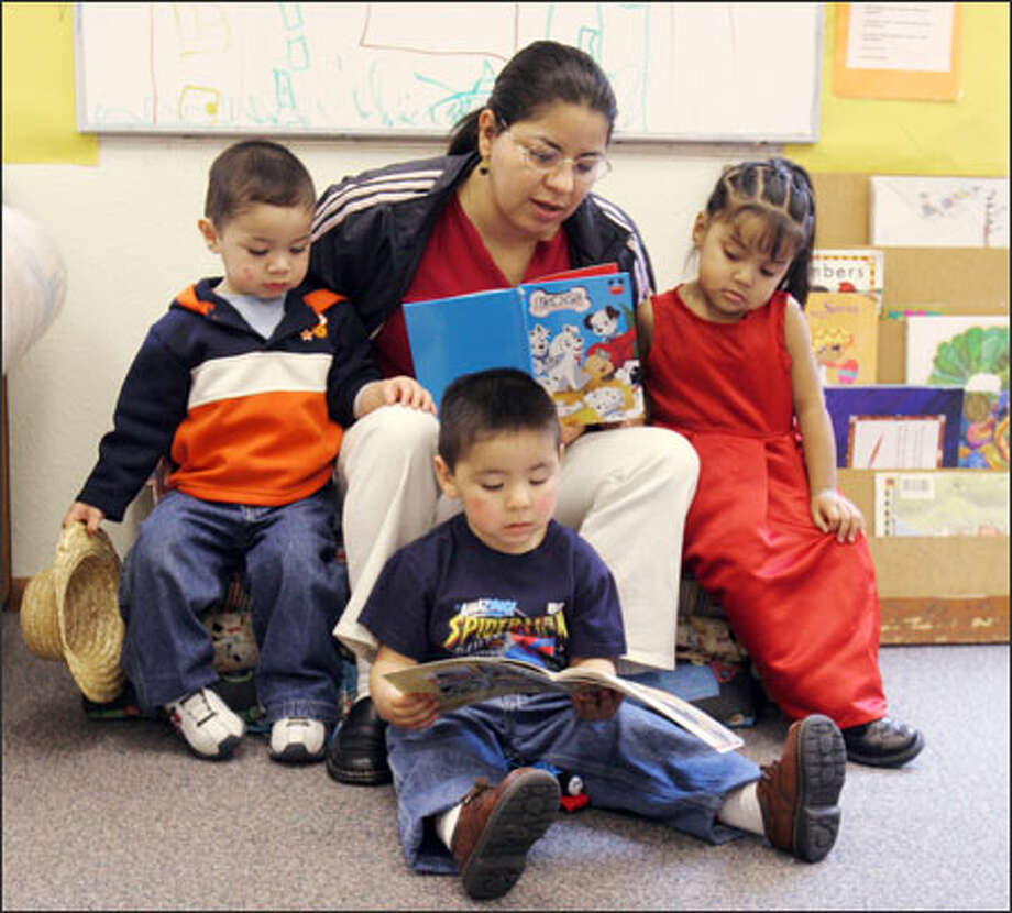 Shoreline Family Support Center's Silvia Calvillo looks down at her son, Andres Ruiz, while she reads with nephew Jose Adrian Calvillo and Paola Medina. Photo: Meryl Schenker/Seattle Post-Intelligencer