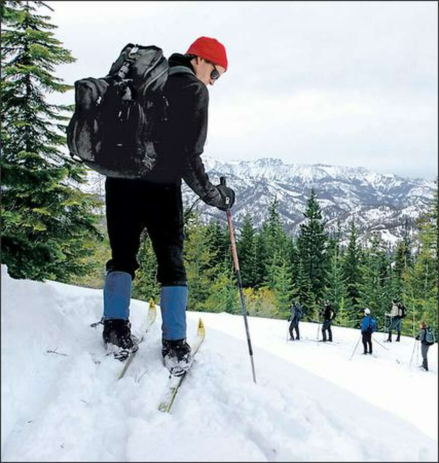 Pico Cantieni checks the terrain in front of him as members of the Ellensburg Cross-Country Ski Club below take in the scenery. Photo: STEVE SHELTON