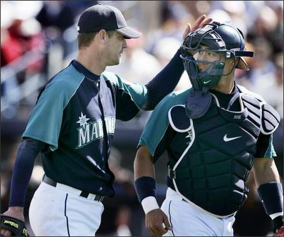 Jamie Moyer congratulates catcher Kenji Johjima after a scoreless third inning against the Giants. Photo: / Associated Press