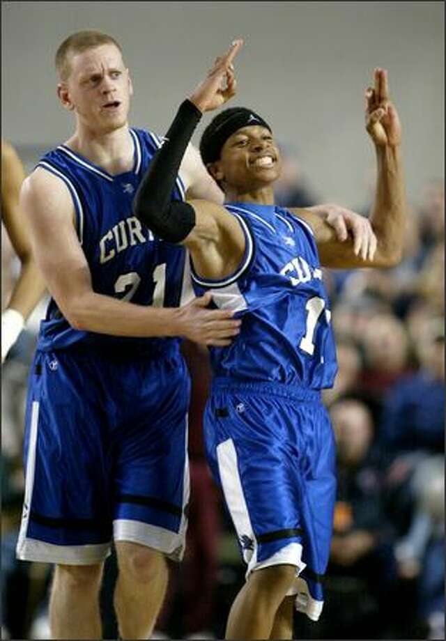 """Isaiah Thomas, congratulated by Alex Seymour, gives the """"3"""" sign after making a 3-pointer to put Curtis ahead 63-56 with 3:50 to go. Photo: Scott Eklund/Seattle Post-Intelligencer"""