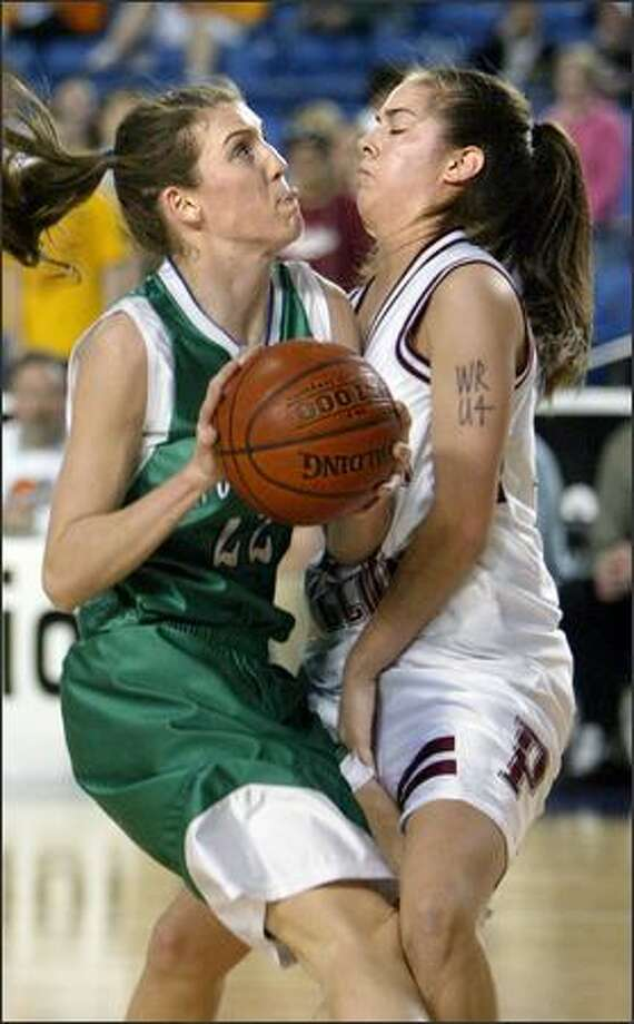 Woodinville's Amanda Fleischman, left, drives into Ashley Corral of Prairie. Photo: Scott Eklund/Seattle Post-Intelligencer