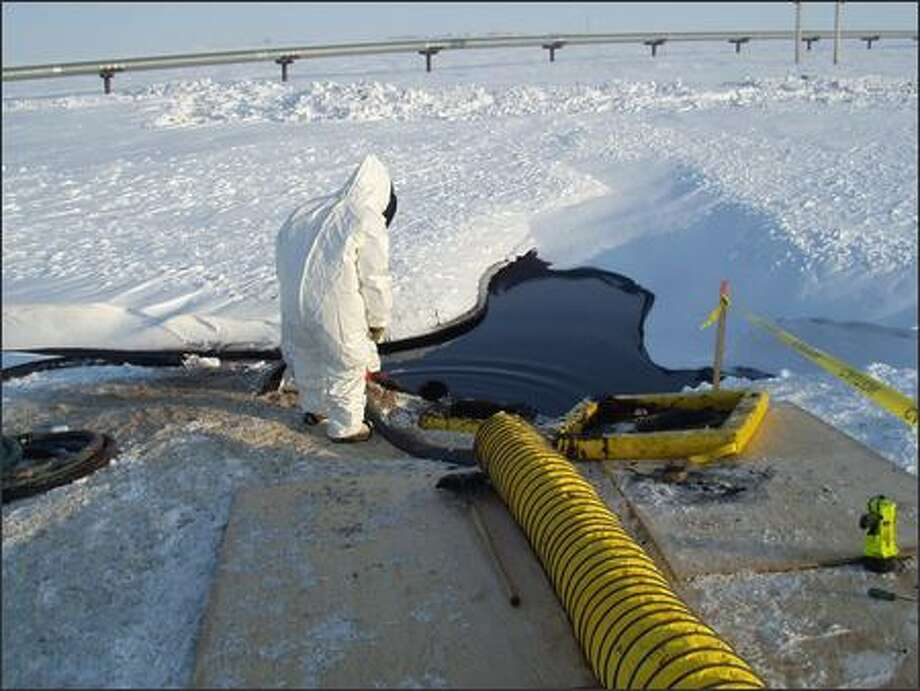 In this photo released by BP Exploration (Alaska) Inc., a worker examines oil spilled from a ruptured transit line in Prudhoe Bay. Photo: / Associated Press