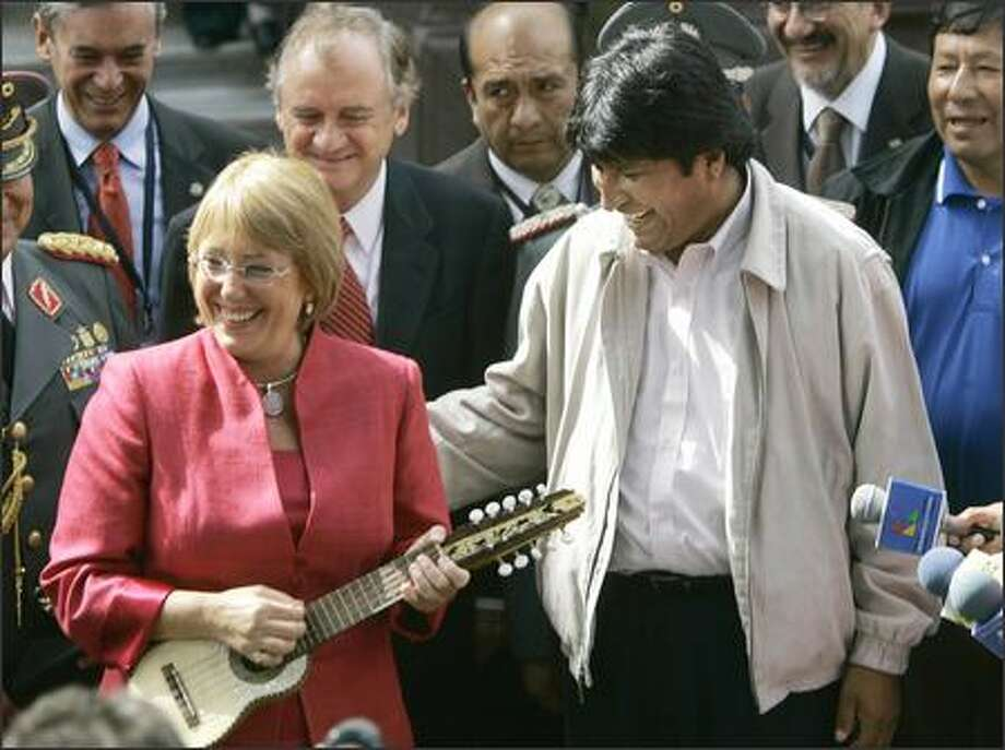 President-elect Michelle Bachelet accepts a Charango guitar Friday from Bolivian President Evo Morales on the eve of her inaugural. Photo: / Associated Press