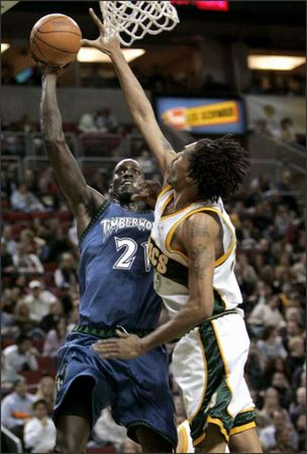 Timberwolves star Kevin Garnett puts up a shot against Mikki Moore during the first half at KeyArena. Garnett had 21 points and 11 rebounds. Photo: / Associated Press