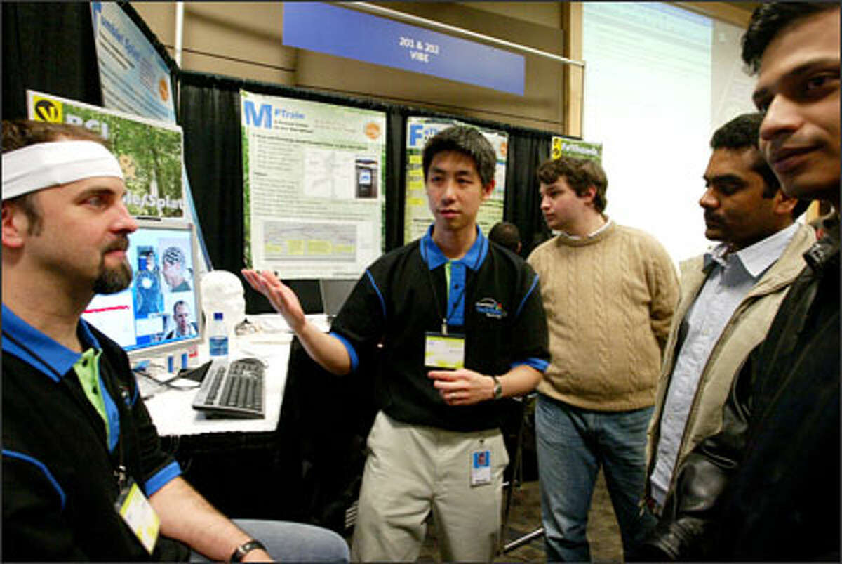 Microsoft researchers Ed Cutrell, left, and Desney Tan, center -- at the recent Microsoft TechFest -- demonstrate their brain-computer interface, which can detect a computer user's cognitive state by sensing electrical impulses and then make adjustments accordingly.