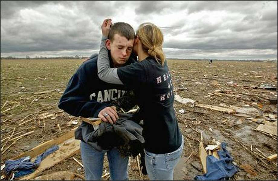 Chris Longdon, 17, left, is hugged by a friend, Katlyn Kendall, near Renick, Mo., after a tornado killed his girlfriend's parents on Sunday. Photo: / Associated Press