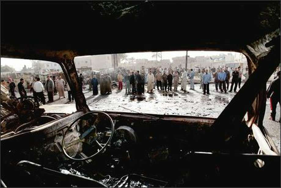 Iraqis view burned cars Monday at the site of the bomb explosions Sunday in Sadr City. Iraqis await the convening of parliament Thursday. Photo: / Associated Press