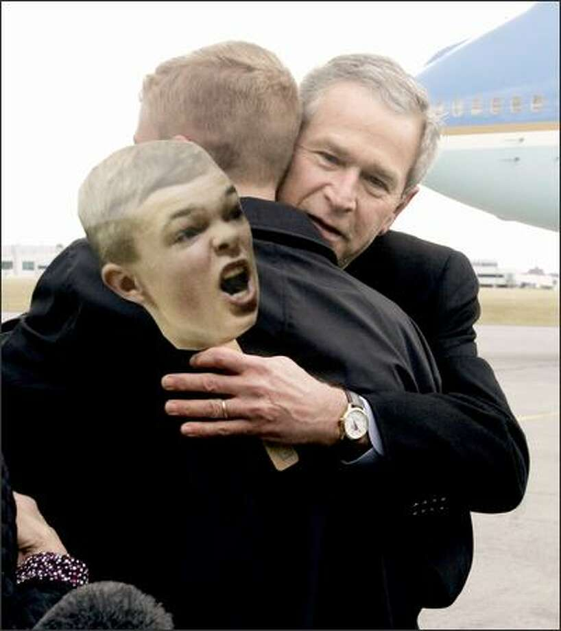 President Bush hugs autistic high school senior Jason McElwain, whose image is seen on the cutout, in Rochester, N.Y., on Tuesday. McElwain, manager of his school's basketball team, was added to the roster for the final game -- and scored 20 points in 4 minutes. Photo: / Associated Press
