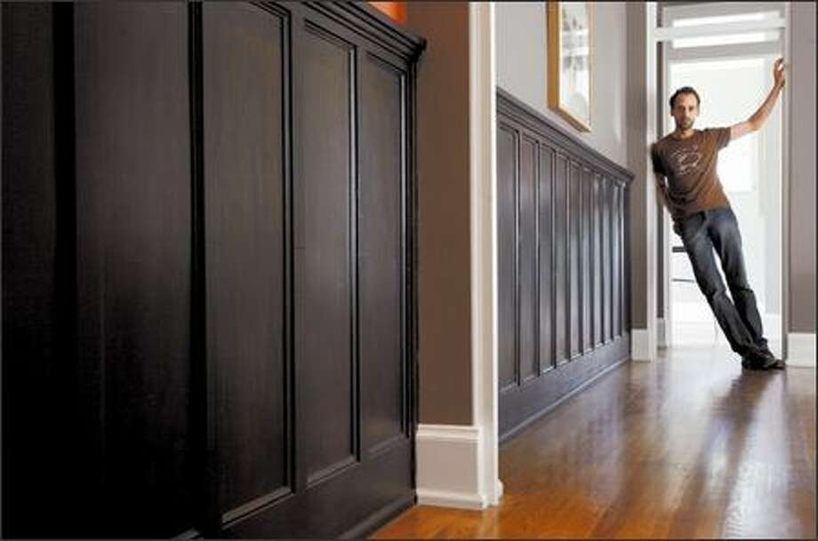 Architect Jean-Francois Godbout, above, put a coat of paint on some wainscoting he bought at Earthwise and installed it in his hallway, dining room and an upstairs wall. Photo: Mike Urban/Seattle Post-Intelligencer