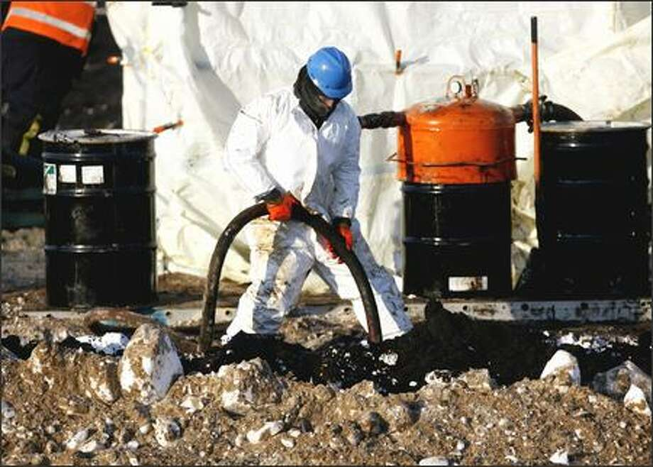 A worker braves merciless cold as he vacuums up some of the 267,000 gallons of oil that spilled at Alaska's Prudhoe Bay oil field. Photo: / Associated Press