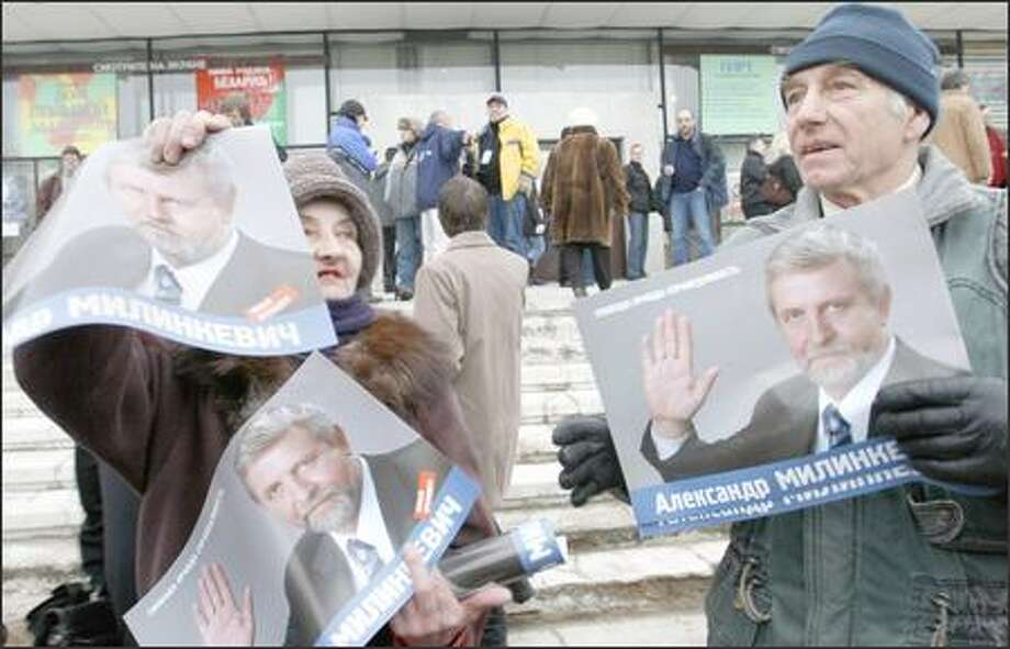 Belarusian supporters of opposition leader Alexander Milinkevich distribute his posters Friday in advance of Sunday's elections. Photo: / Associated Press