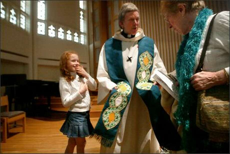 The Rev. Barry Keating of Maplewood Presbyterian Church, with daughter Shea, thanks Mary Charles for making the stole he wore at Friday's Mass. Photo: Karen Ducey/Seattle Post-Intelligencer