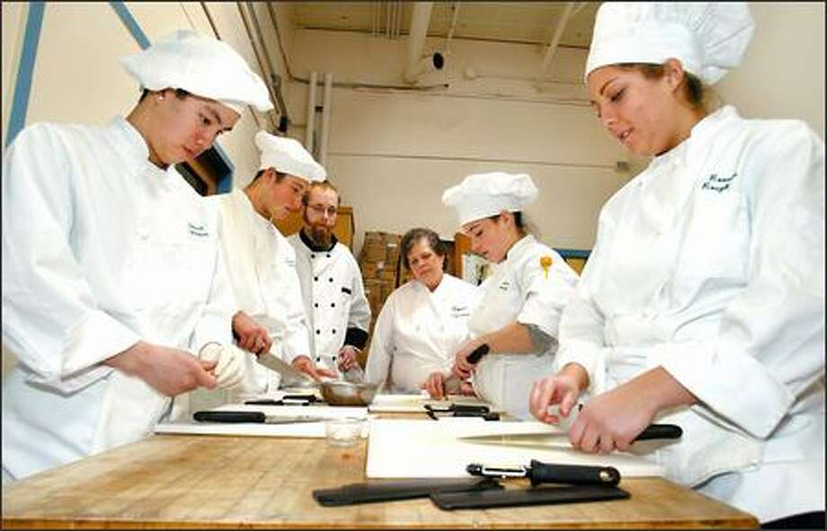 Roosevelt High School students go over knife skills under the watchful eyes of their teacher and a guest chef as they prep for the upcoming competition. From left: Alex Kong, student; Ilya Kiselev, student; chef Wilson Bauer; teacher Carolyn Garthwaite; and students Emily Munday and Courtney Marotto. Photo: Gilbert W. Arias/Seattle Post-Intelligencer