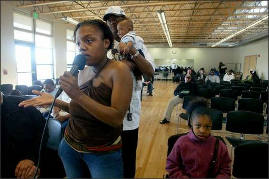 Patrice Thomas spoke Monday during a field hearing with FEMA officials to address the needs of Hurricane Katrina evacuees now living in Washington. Behind Thomas is her boyfriend, Jarrett Bazile, holding their 8-month-old son, Julian Bazile, and next to Thomas is her daughter, Che'Reonna Thomas. Photo: Karen Ducey/Seattle Post-Intelligencer