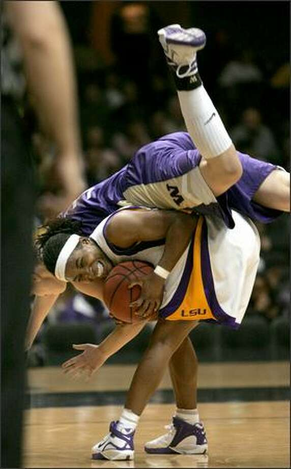 Washington forward Breanne Watson flips over LSU guard Erica White as they battle for the ball. Watson was called for a foul. Photo: / Associated Press