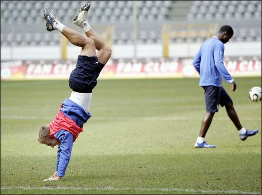 "U.S. player Taylor Twellman, turning a handstand during practice Tuesday in Dortmund, said of the Germans, ""They're going to come out flying."" Photo: / Associated Press"