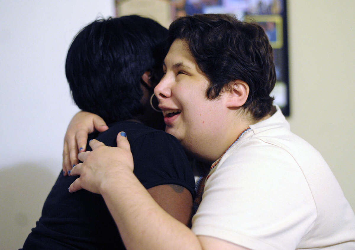 Carol Larson (right) embraces Myrtle Edwards, who helps care for her at the group home.