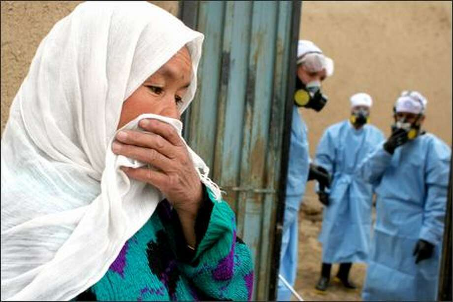 A woman covers her nose and mouth as workers spray disinfectant inside her home near Kabul, Afghanistan. An outbreak of a deadly bird flu was confirmed earlier this month. Photo: / Associated Press